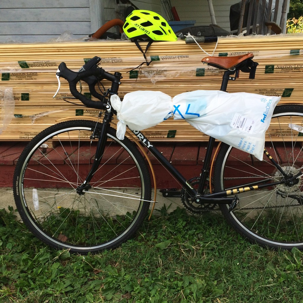 A back bike has a white roll of posters tied to the top tube leans against a stack of lumber.